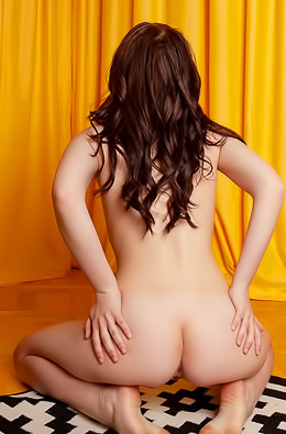 Brunette takes twisted positions on yellow couch